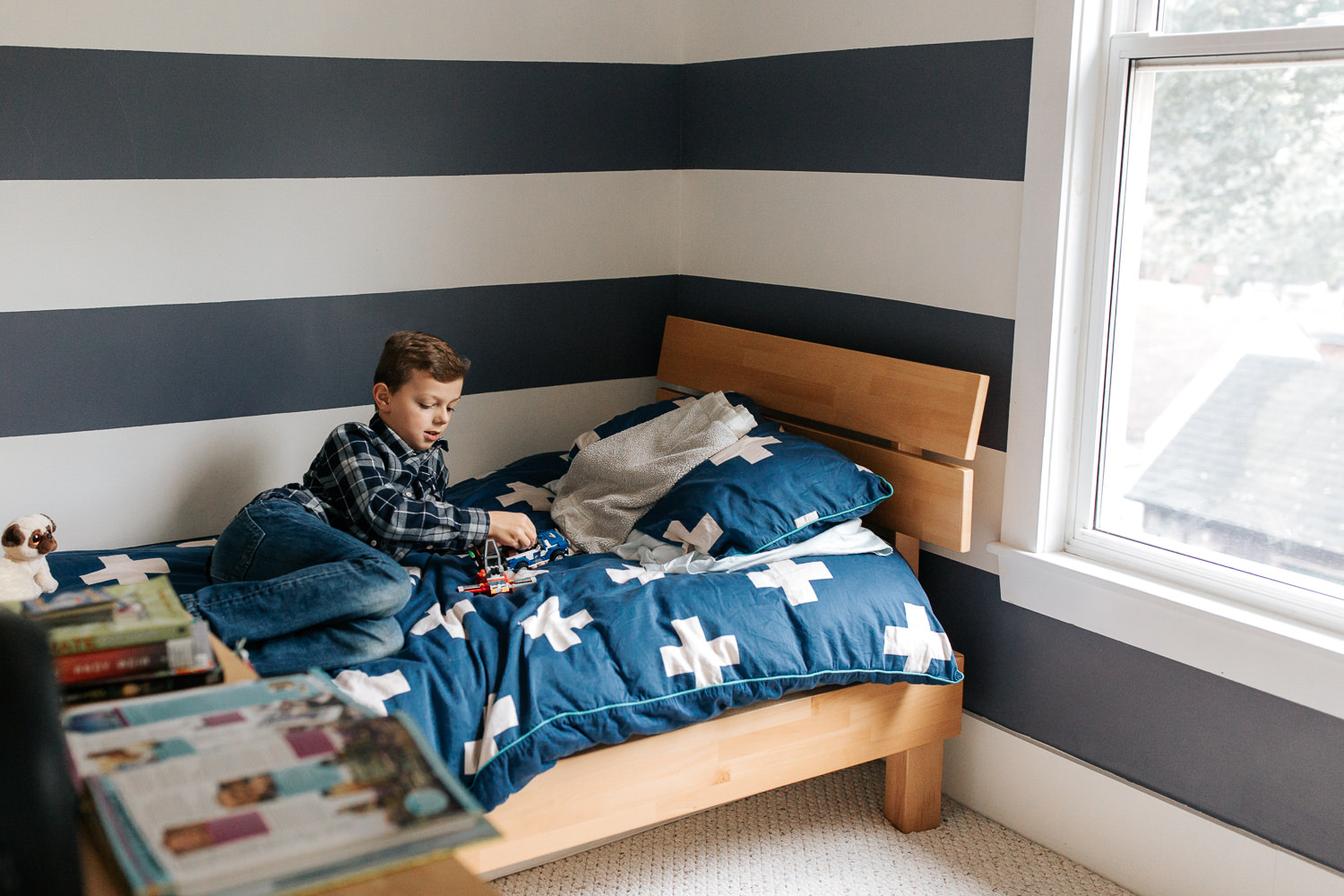 9 year old boy in plaid shirt with light brown hair lying on bed in blue and white room playing with lego - Barrie In-Home Photography