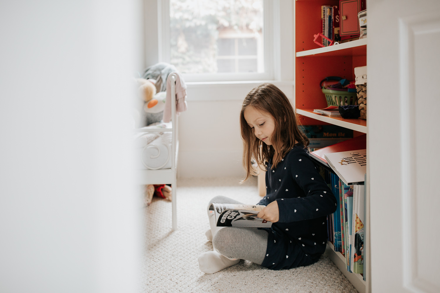 7 year old girl in polka dot dress with brown hair sitting on floor of bedroom leaning against orange and white bookcase and reading book - Stouffville In-Home Photos