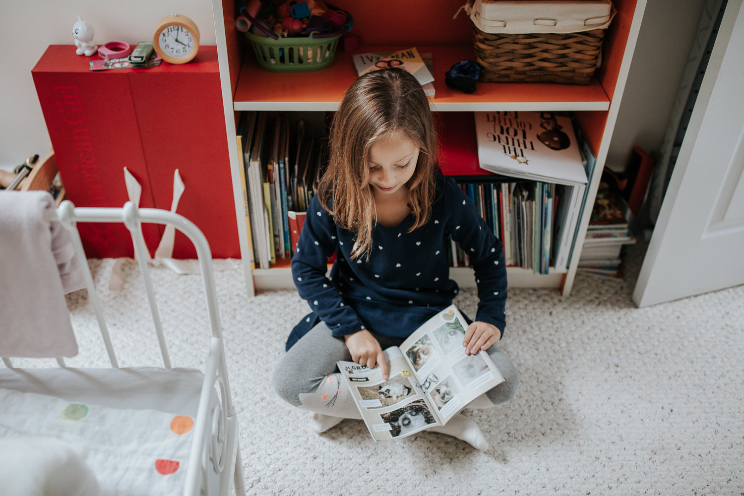 7 year old girl in polka dot dress with brown hair sitting on floor of bedroom leaning against orange and white bookcase and reading book - Markham In-Home Photos