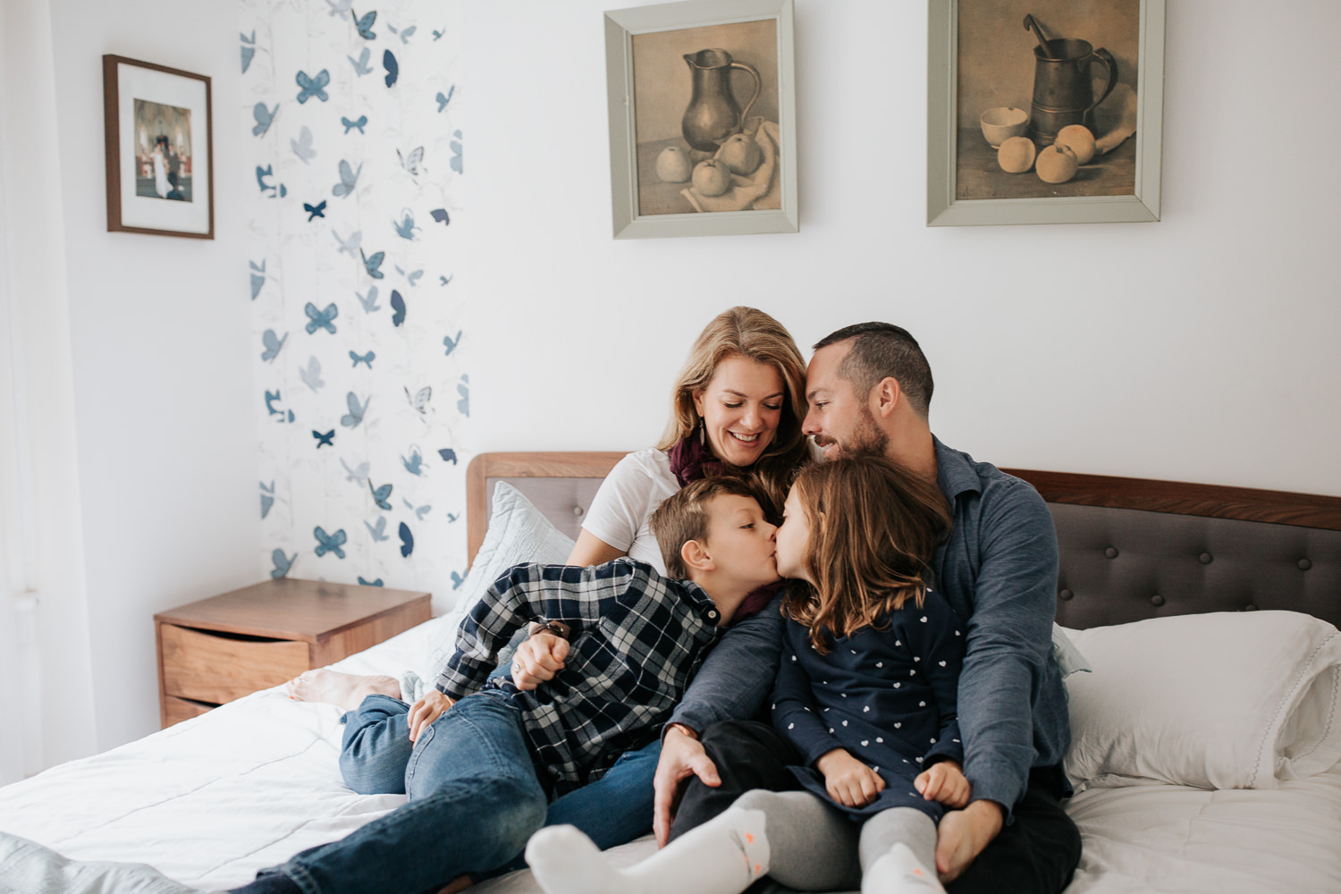 family of 4 sitting on master bed, 7 year old girl sitting in dad's lap, 9 year old boy in mom's, brother giving little sister a kiss - Newmarket Lifestyle Photography