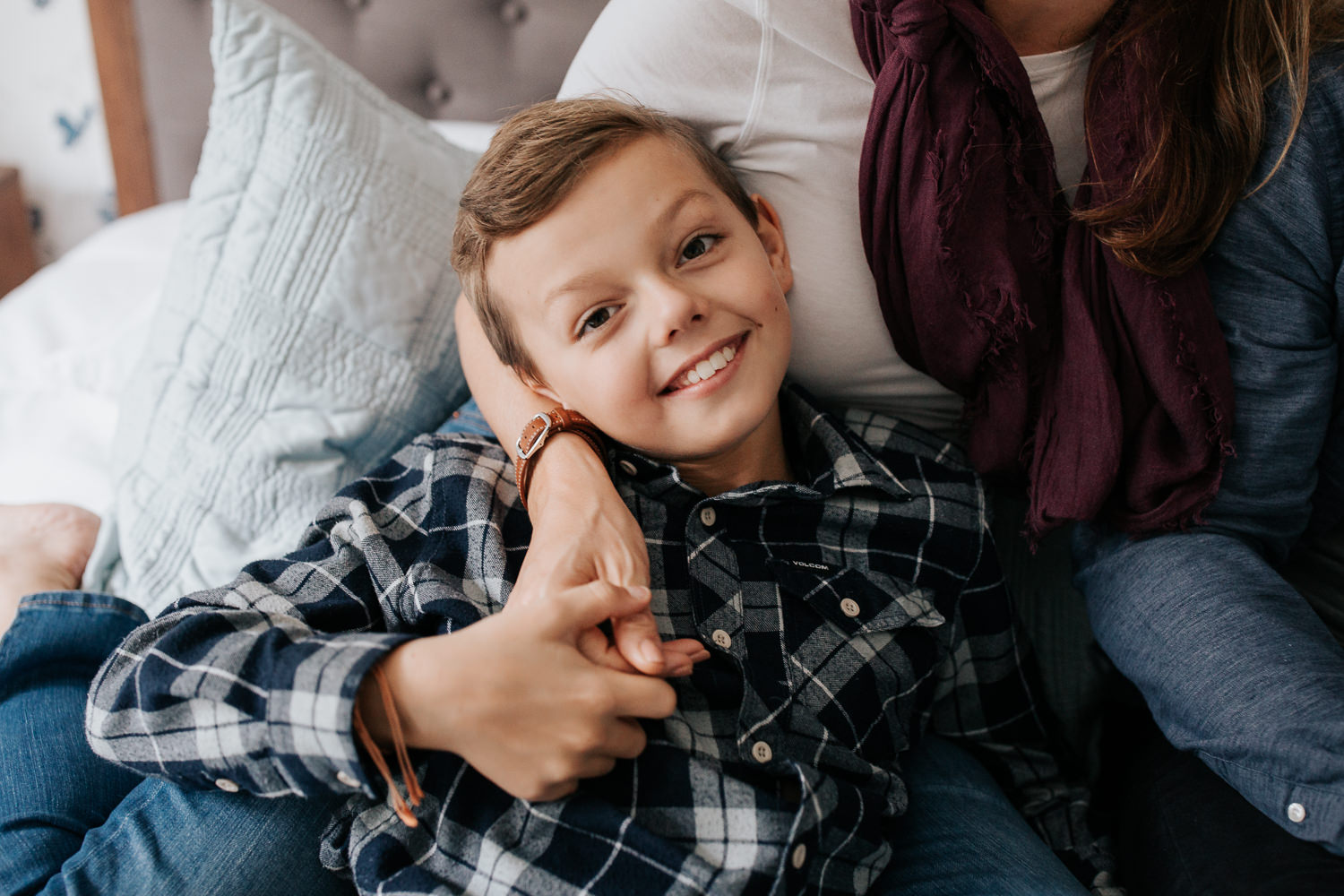 9 year old boy lying in mom's lap as they sit on bed, looking up and smiling at camera - Stouffville Lifestyle Photography
