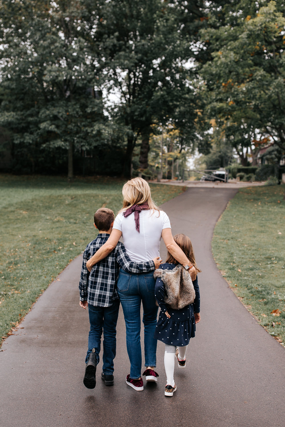 mom walking down paved path at city park, arms around 9 year old son and 7 year old daughter as they stroll - Newmarket Lifestyle Photography