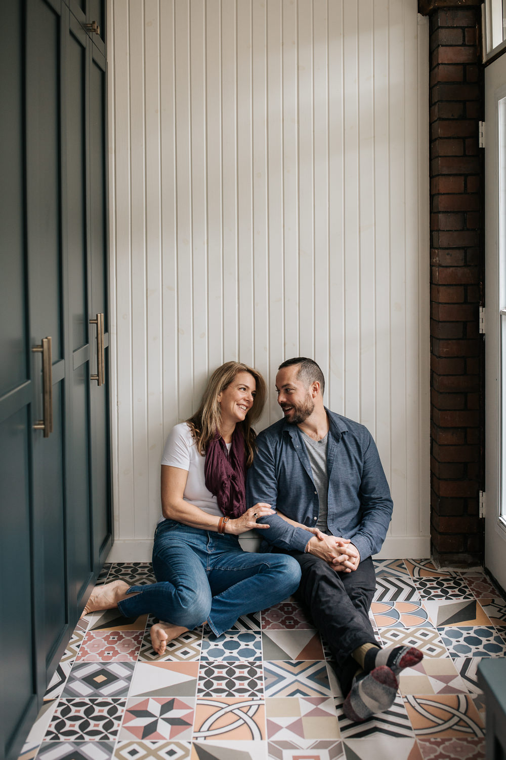 husband and wife sitting on ground of colourful tile, leaning against white wall, arms linked and holding hands, smiling at one another -Barrie Lifestyle Photos