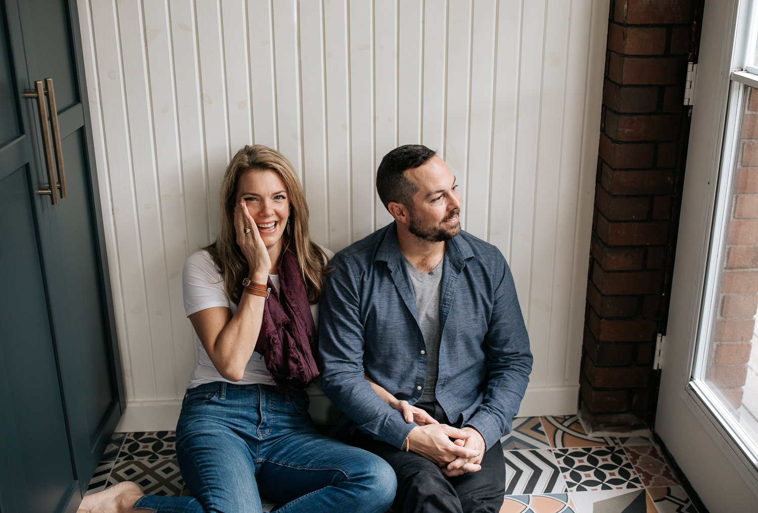 husband and wife sitting on ground of colourful tile, leaning against wall, arms linked, holding hands, man looking to side, woman's hand on cheek smiling at camera  -York Region Lifestyle Photos
