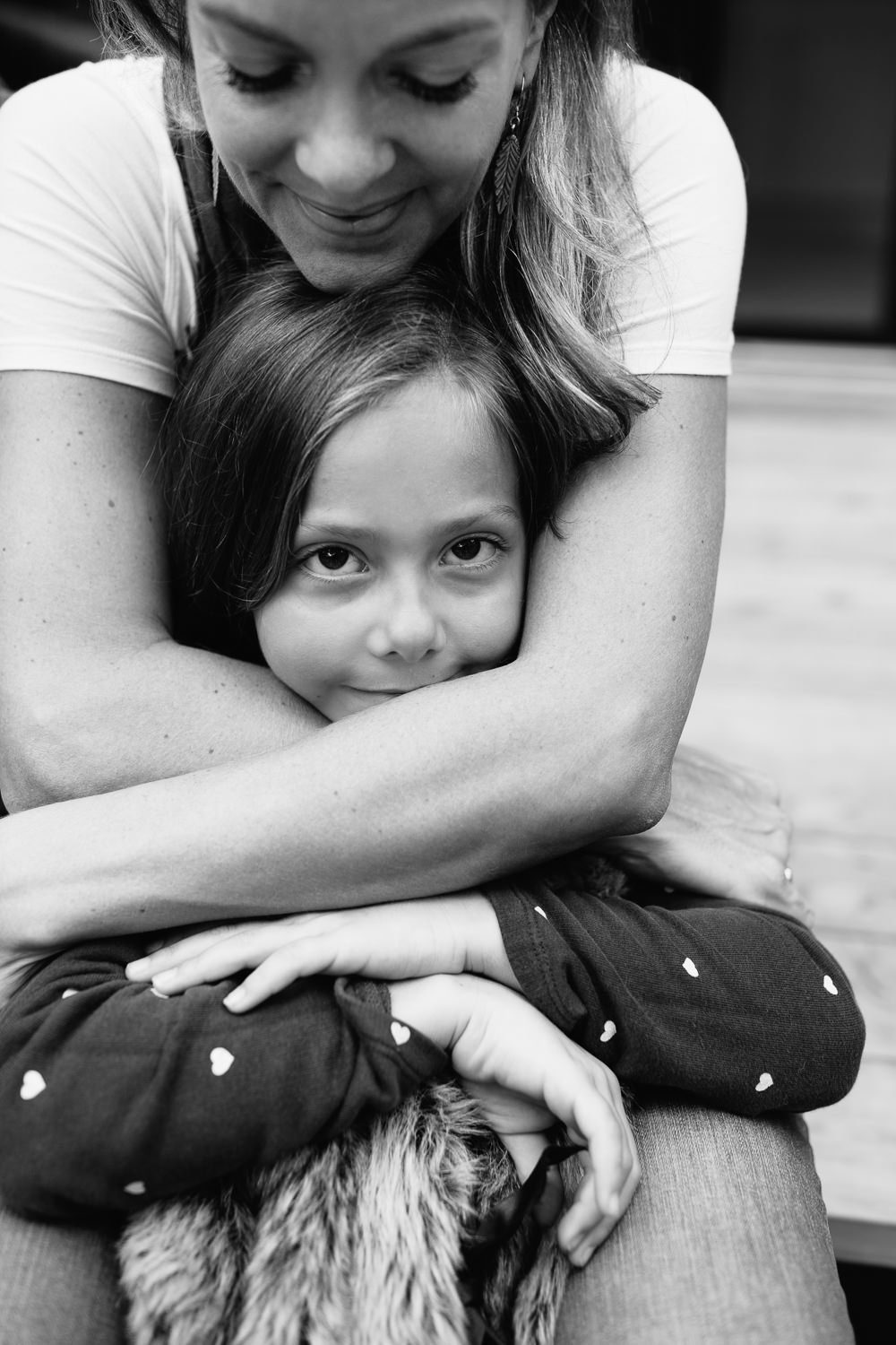 mother and daughter sitting on steps of backyard porch, mom's hugging 7 year old girl's shoulders, girl looking at camera -Stouffville In-Home Photography