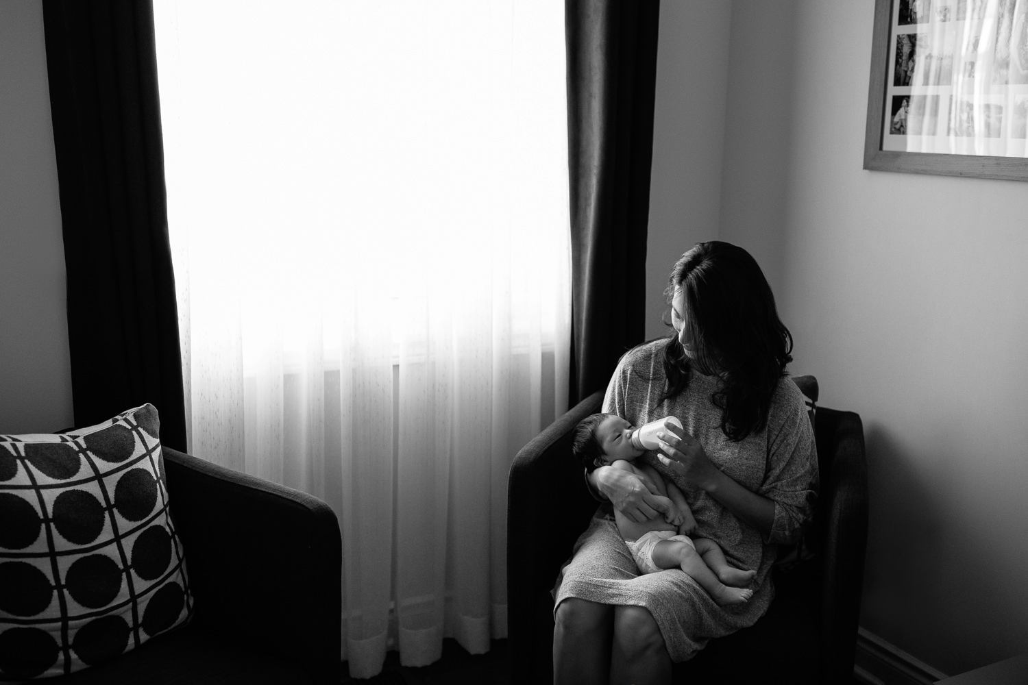 mom with long dark hair sits in armchair next to window feeding 2 week old baby boy in diaper a bottle - Stouffville In-Home Photos