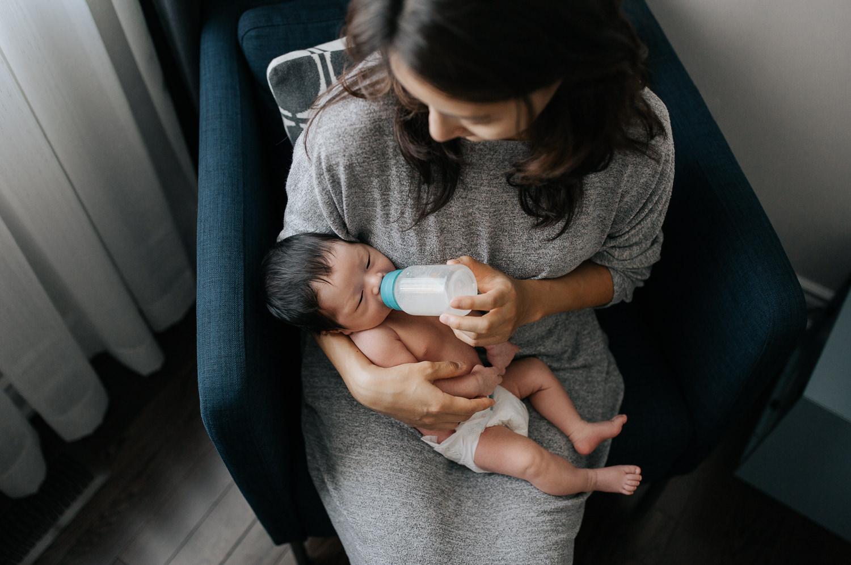 mom with long dark hair sits in blue armchair feeding 2 week old baby boy in diaper a bottle - Uxbridge In-Home Photos