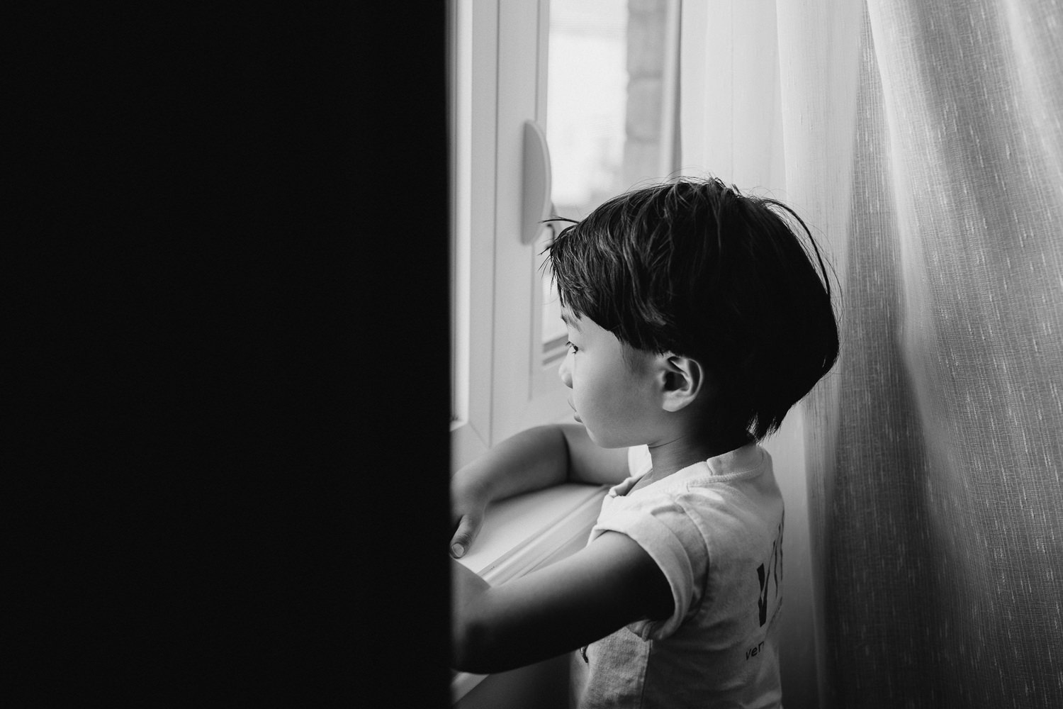 3 year old boy with dark hair and eyes wearing light t-shirt standing at window looking outside - GTA In-Home Photos