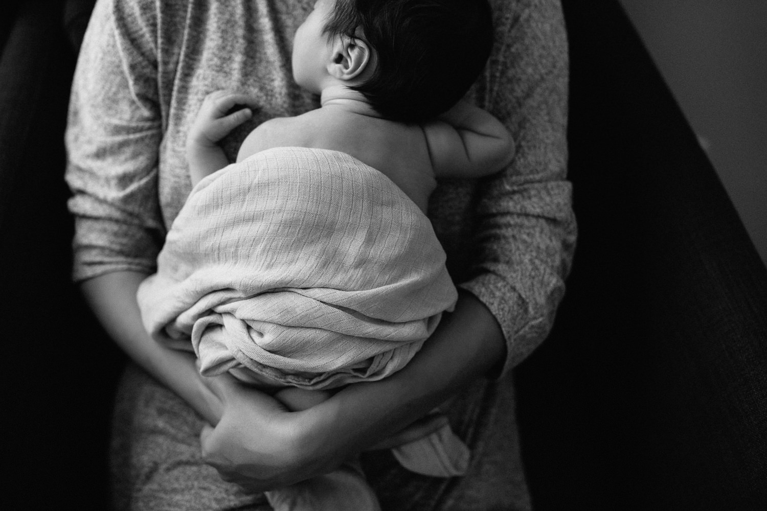 mother sitting in armchair snuggling 2 week old sleeping baby boy to her chest, son wrapped in swaddle - Newmarket Lifestyle Photos