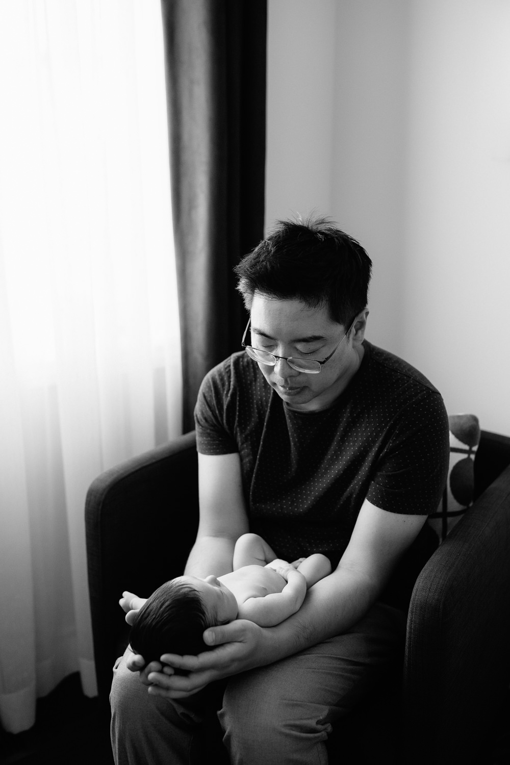 father sitting in armchair holding sleeping 2 week old baby boy in diaper, son's head in dad's hands - Uxbridge Lifestyle Photography