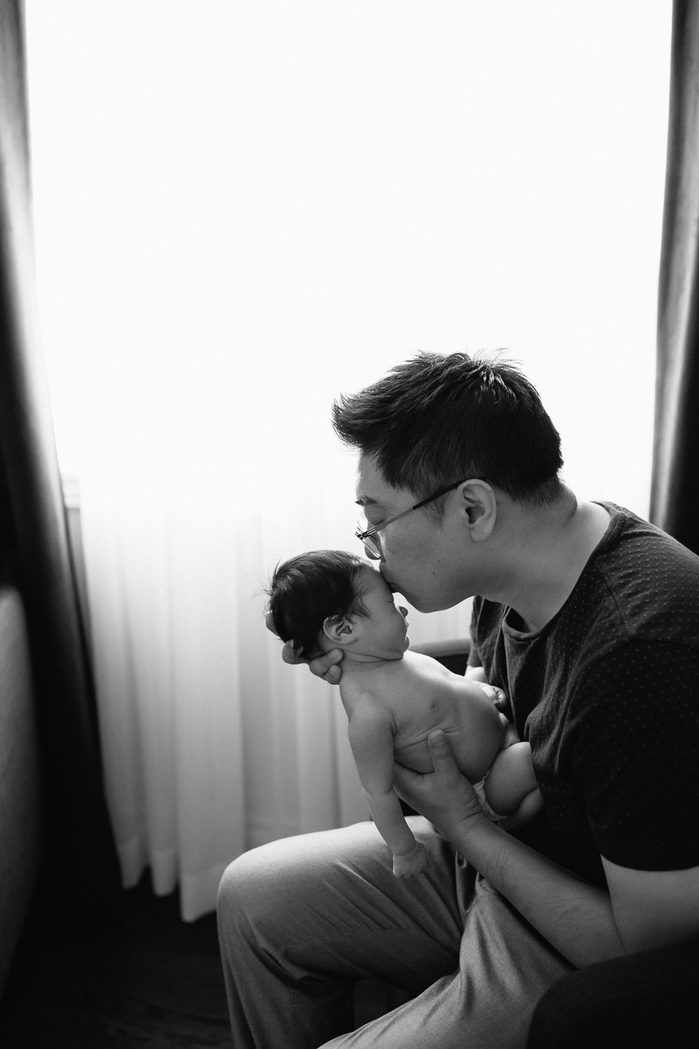 father sitting in armchair holding sleeping 2 week old baby boy in diaper up to his face and kissing his forehead - Markham Lifestyle Photography