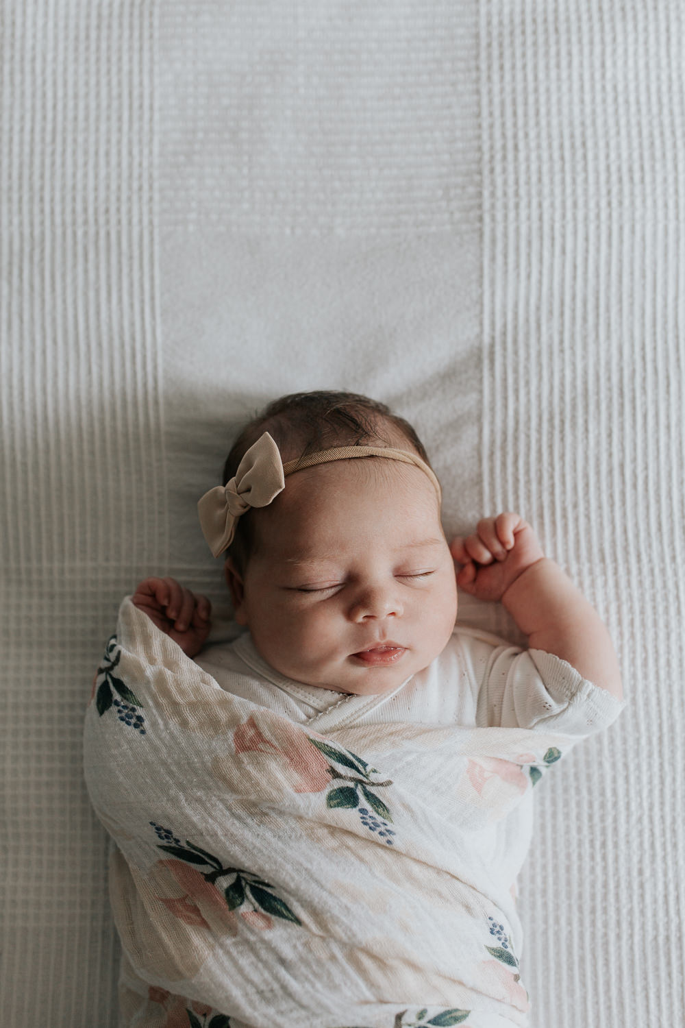 2 week old baby girl with dark hair wrapped in swaddle with soft pink flowers, wearing bow headband asleep on bed, hands near face - Stouffville In-Home Photography