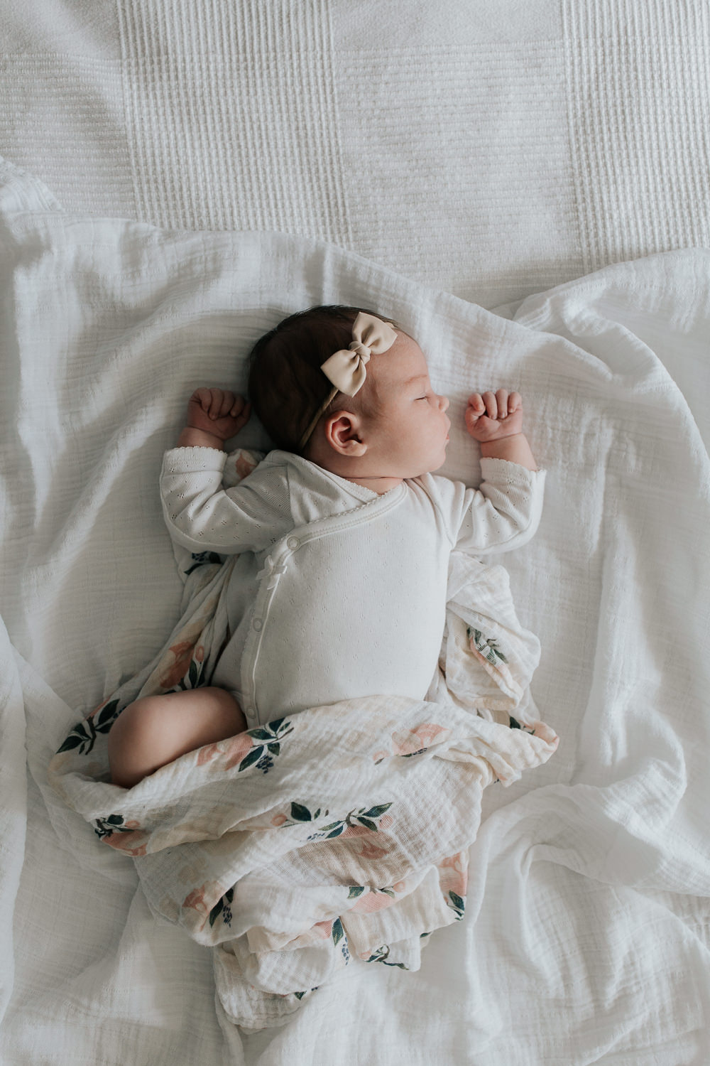 2 week old baby girl with dark hair in white onesie lying on swaddle with soft pink flowers, wearing bow headband asleep on bed, hands near face - Markham In-Home Photography