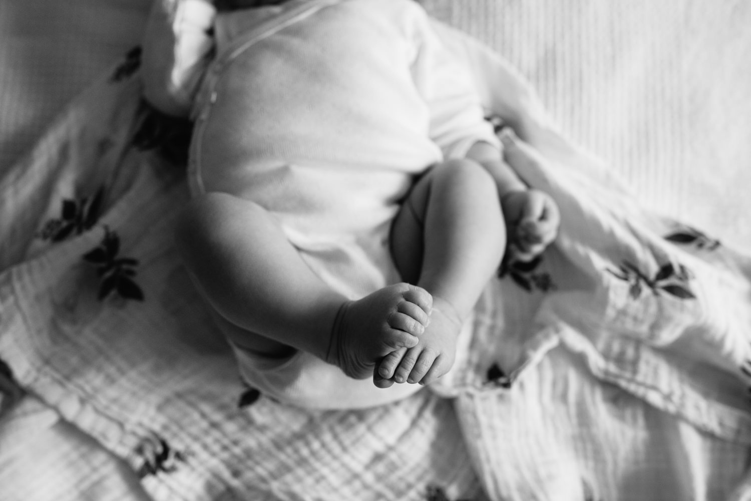 2 week old baby girl in white onesie lying on bed, close up of bare feet -Barrie In-Home Photography