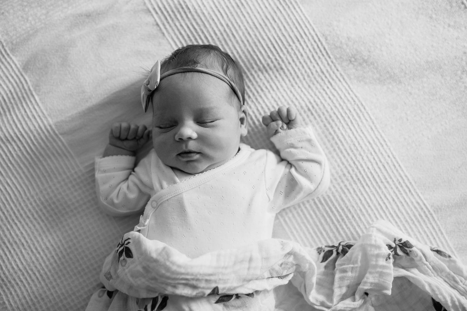 2 week old baby girl with dark hair in white onesie lying on swaddle, wearing bow headband asleep on bed, hands near face -York Region In-Home Photography