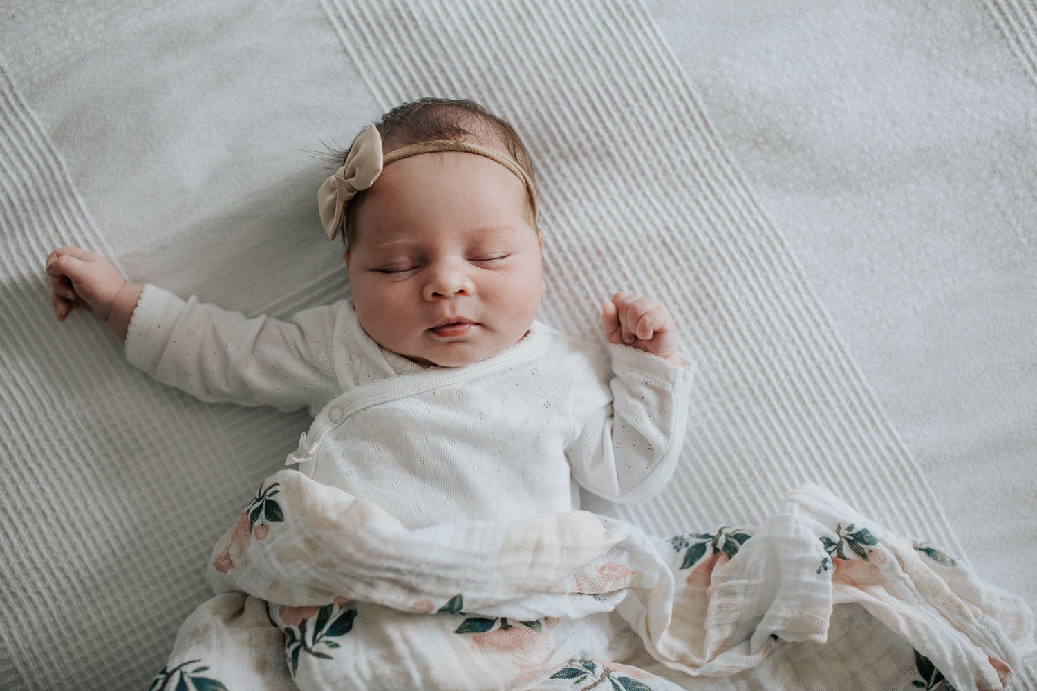 2 week old baby girl with dark hair in white onesie lying on swaddle with soft pink flowers, wearing bow headband asleep on bed, hands near face -Newmarket In-Home Photos