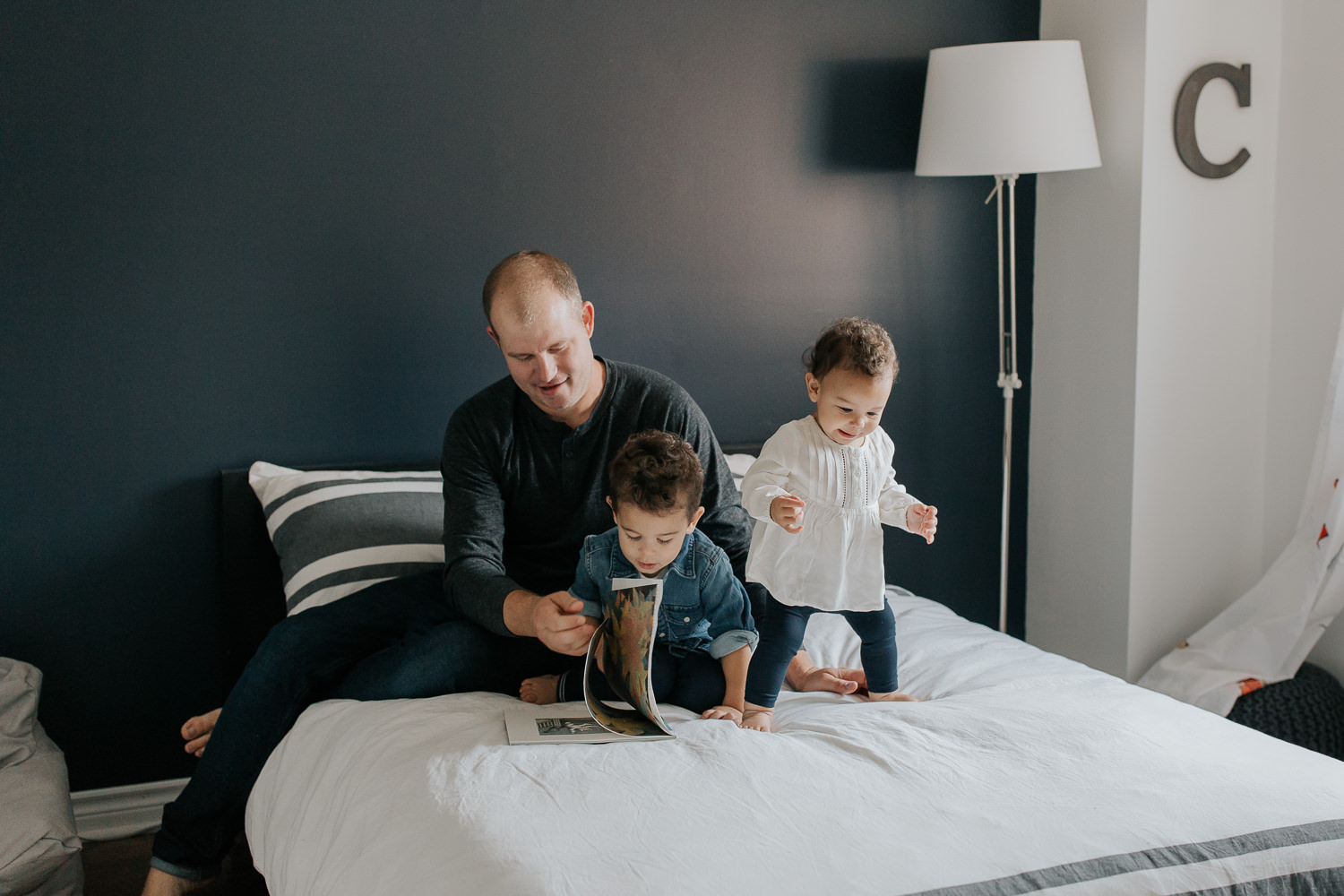 father sitting on bed with 2 year old son reading a story, 1 year old daughter standing next to them, jumping - Stouffville In-Home Photos