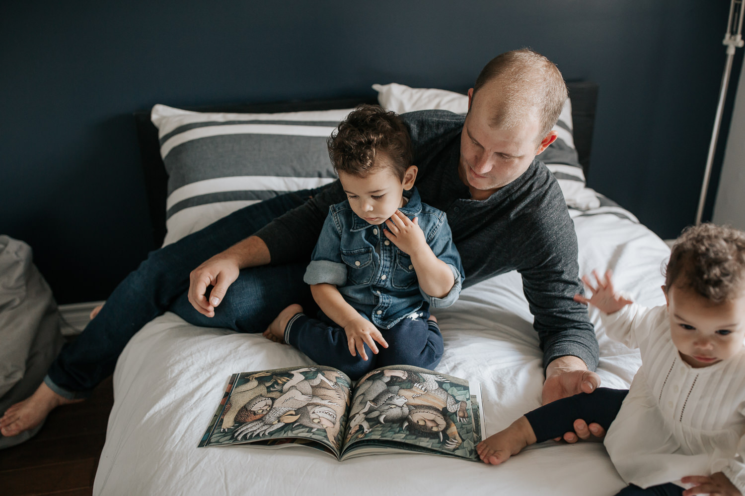 father sitting on bed with 2 year old son reading a story, 1 year old daughter sitting next to them, dad's hand holding her leg - GTA In-Home Photos