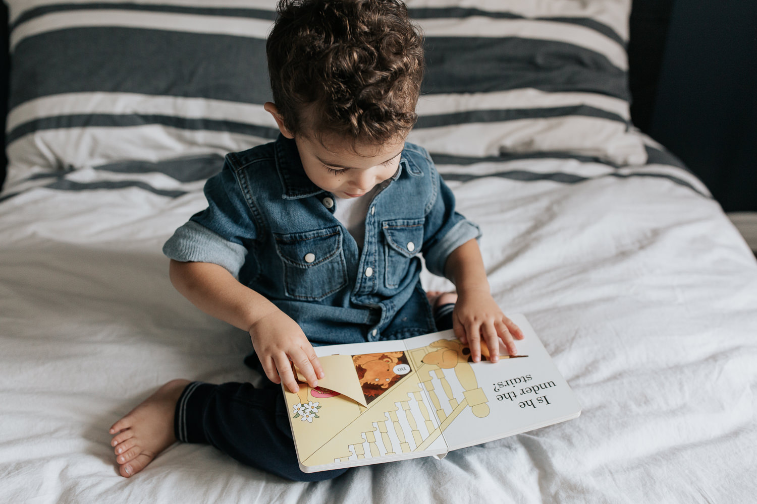 2 year old toddler boy with dark curly hair wearing chambray shirt sitting on his bed reading book - York Region In-Home Photos