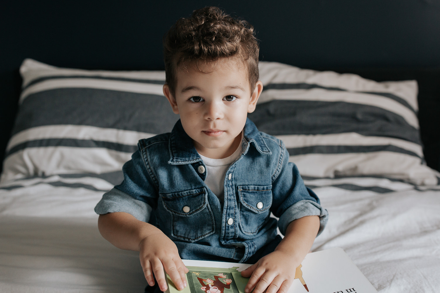 2 year old toddler boy with dark curly hair wearing chambray shirt sitting on his bed holding book and looking at camera - Newmarket Lifestyle Photos