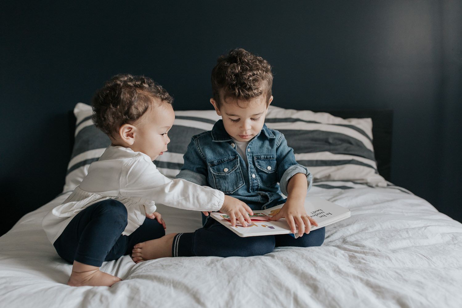 2 year old toddler boy with dark curly hair wearing chambray shirt sitting on his bed reading book, 1 year old baby sister sitting next to him, reaching for the page - Markham Lifestyle Photos