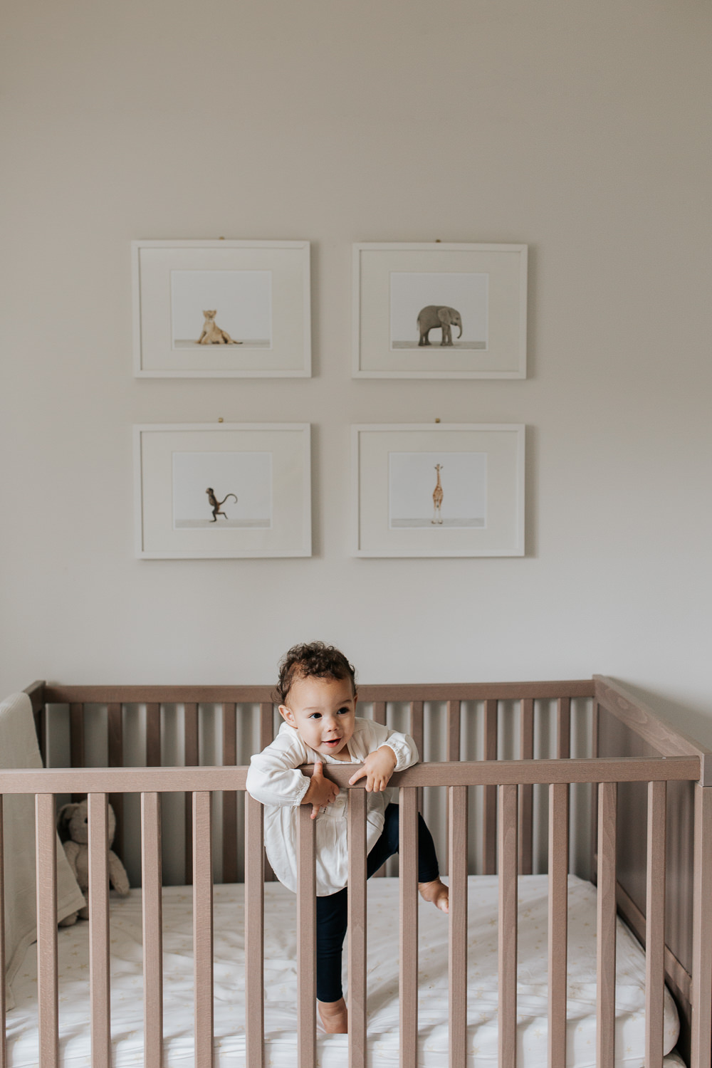 2 year old girl with dark curly hair and brown eyes in cream top and dark pants trying to climb out of crib in neutral nursery with animal prints on wall -GTA Lifestyle Photos