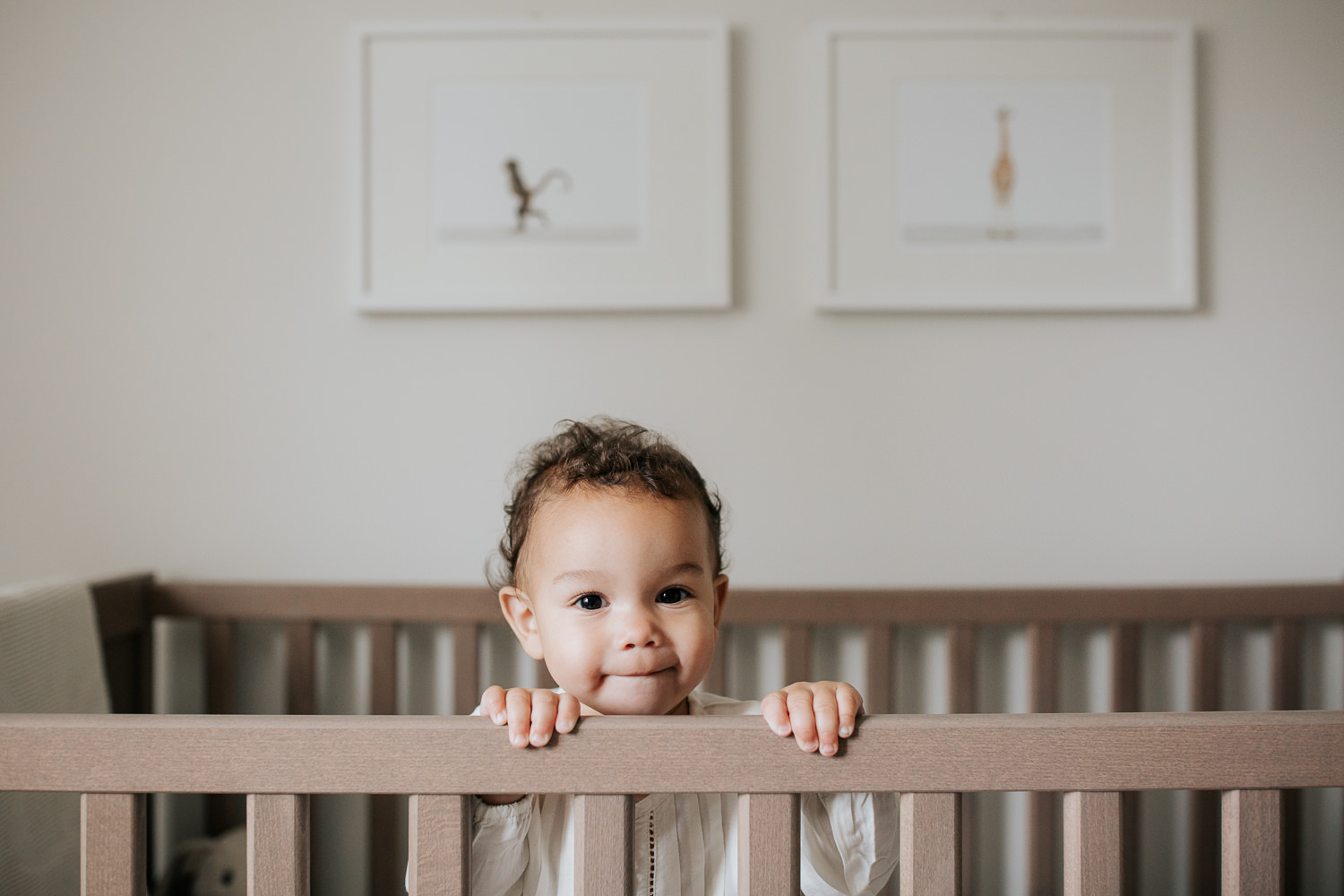 2 year old girl with dark curly hair and brown eyes in cream top and dark pants standing in crib looking at camera in neutral nursery with animal prints on wall -Newmarket Lifestyle Photography