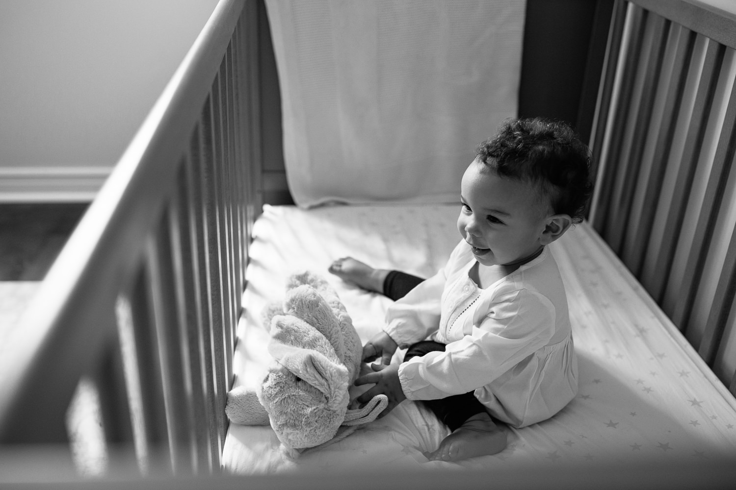 2 year old girl with dark curly hair and brown eyes in cream top and dark pants sitting in crib holding stuffed bunny and smiling -York Region Lifestyle Photos