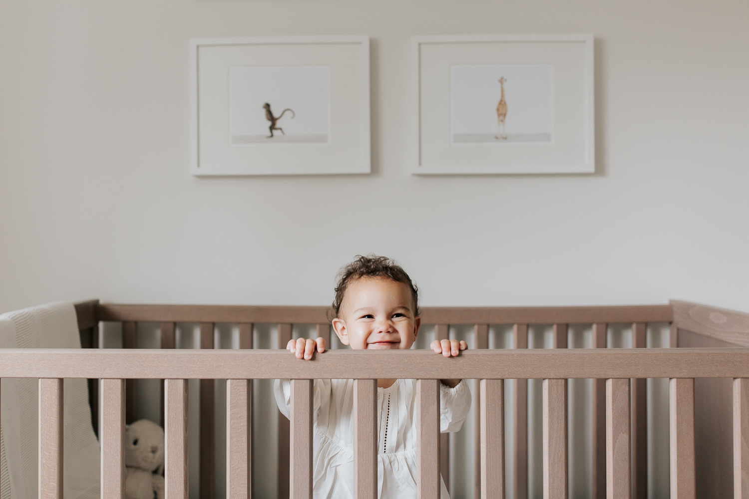 2 year old girl with dark curly hair and brown eyes in cream top and dark pants standing in crib looking up and smiling in neutral nursery with animal prints on wall -Markham Lifestyle Photography