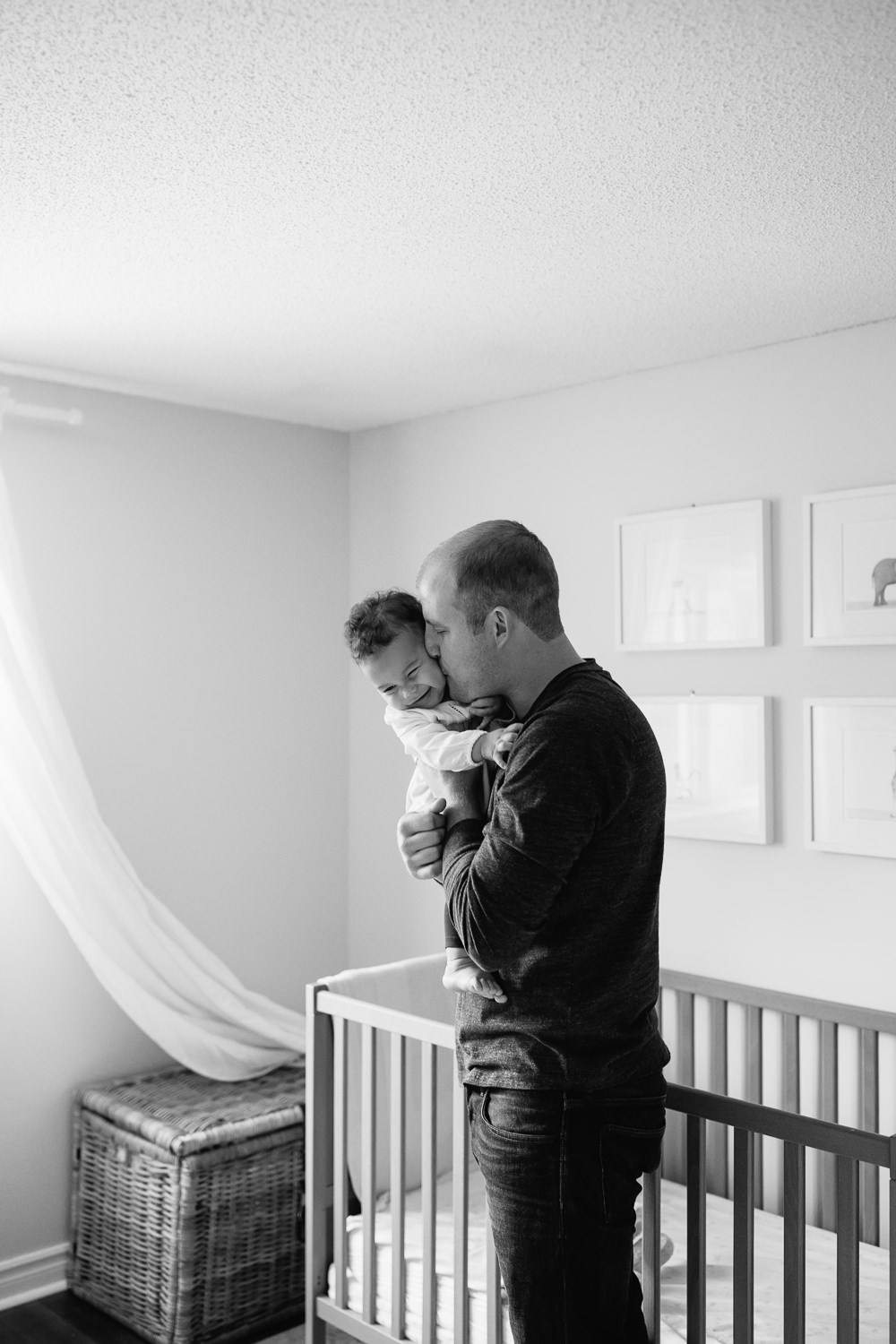 dad standing in nursery in front of crib holding and kissing 1 year old baby girl on the cheek as she laughs -Barrie Lifestyle Photography