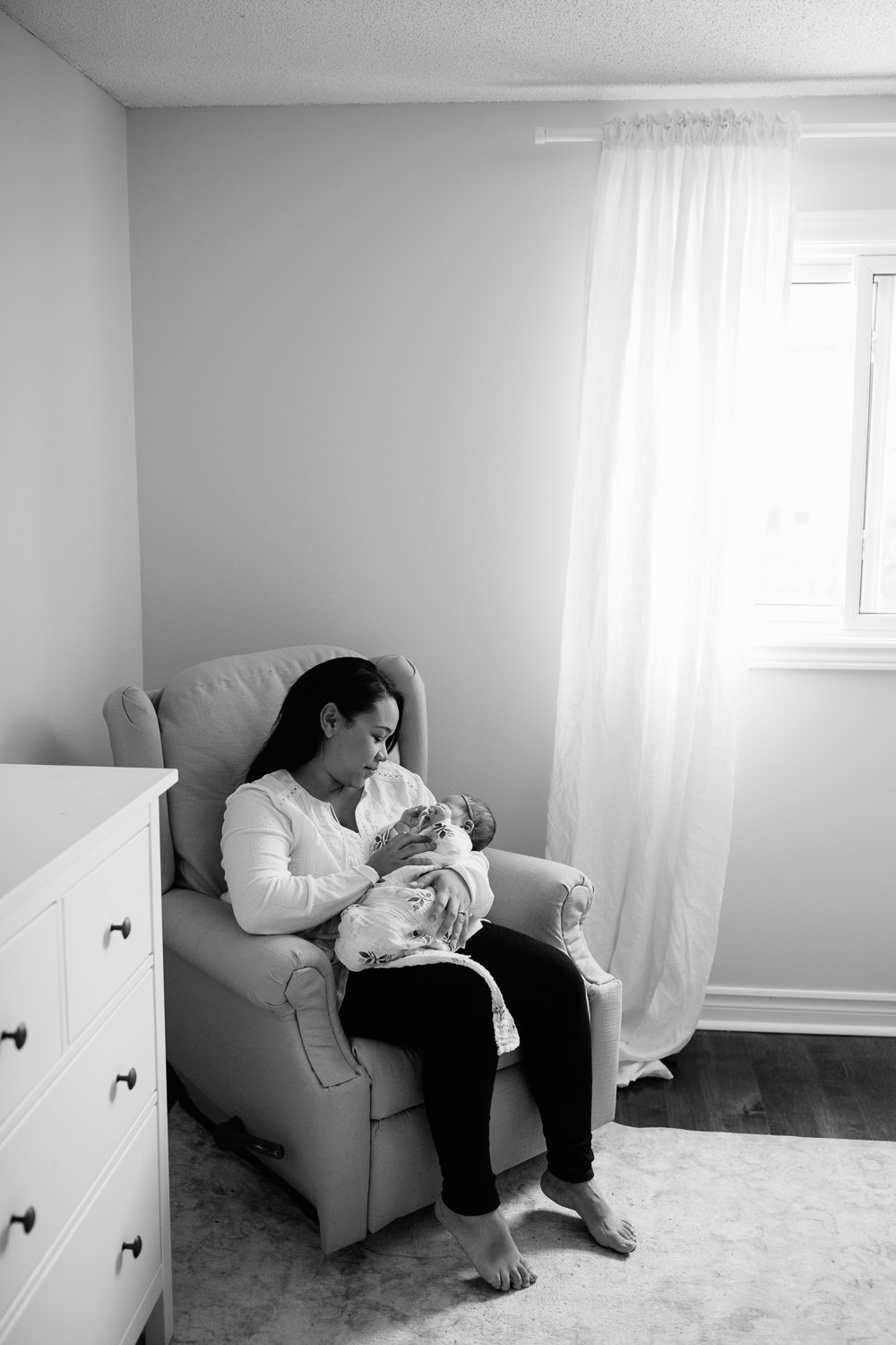 mother sitting in nursery glider chair holding and looking at 2 week old baby girl wrapped in swaddle -GTA Lifestyle Photography