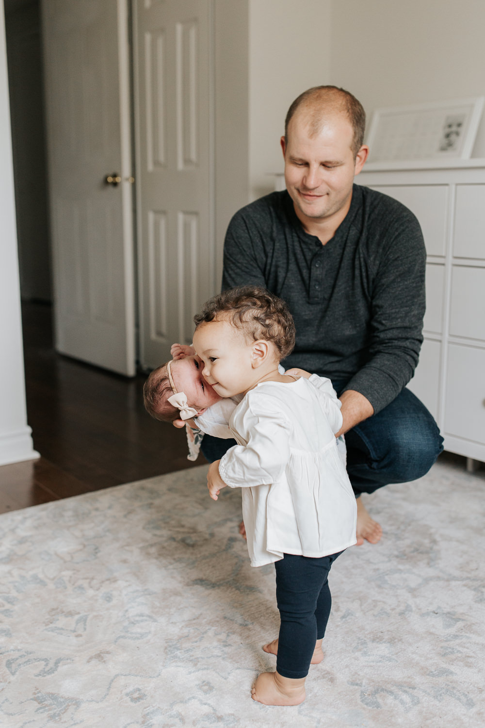 dad holding 2 week old baby girl in his arms, squatting down as 1 year old toddler daughter with dark hair in white top and tights gives little sister a kiss -Barrie In-Home Photography