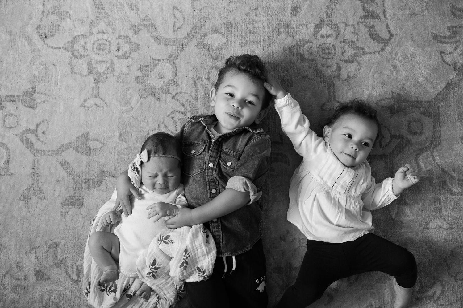 3 siblings lying on floor, 2 week old baby girl held by 2 year old big brother, 1 year old toddler sister next to boy, hand on his head - Markham In-Home Photos