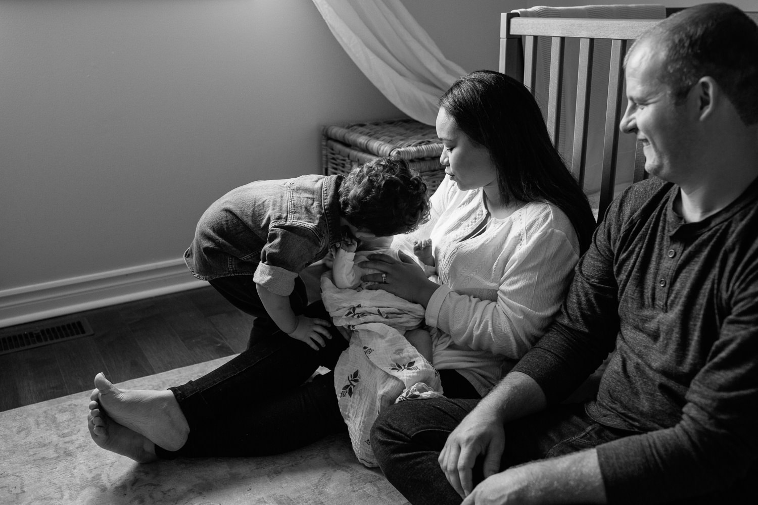 parents sitting on floor of nursery leaning against crib, mom holding 2 week old baby girl in her arms as two year old big brother leans over and kisses little sister - GTA In-Home Photos