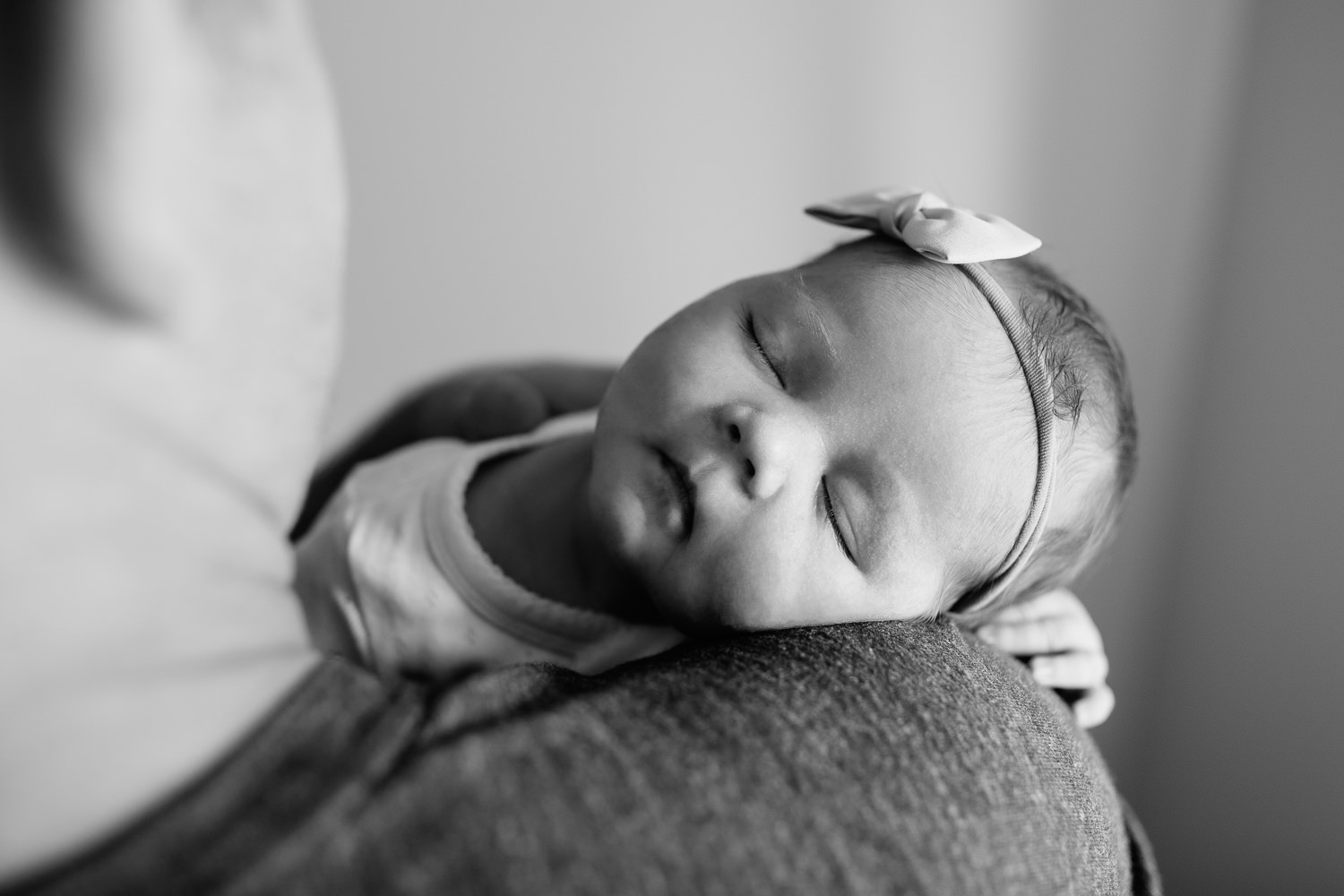 dad sitting on edge of bed holding2 week old baby girl wearing bow headband, sleeping on father's shoulder -Barrie In-Home Photography