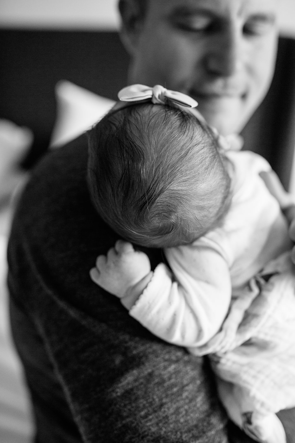 dad sitting on edge of bed holding 2 week old baby girl in onesie and swaddle, sleeping on father's shoulder, close up of hair -GTA In-Home Photography
