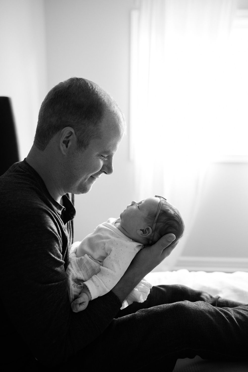 dad sitting on master bed holding 2 week old baby girl's head in his hands, smiling at her, daughter in white onesie with headband on -York Region In-Home Photography