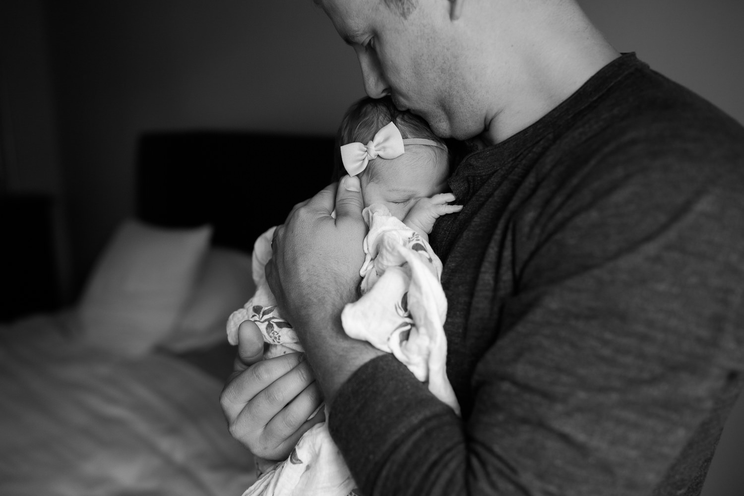 2 week old baby girl wrapped in swaddle sleeping on dad's chest, father kissing daughter on top of head - Newmarket Lifestyle Photos