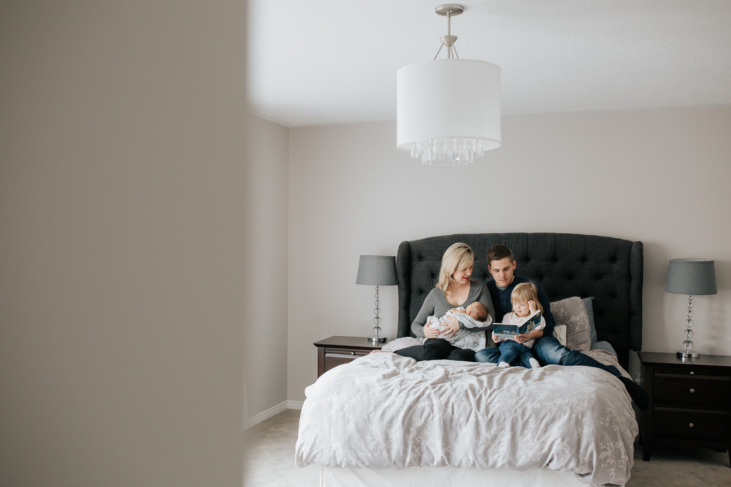 family of four sitting on bed, mom holding 2 week old baby boy 2 year old girl sitting on dad's lap reading story book - York Region Lifestyle Photography