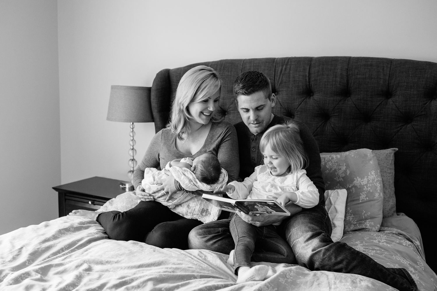 family of four sitting on bed, mom holding 2 week old baby boy 2 year old girl sitting on dad's lap reading story book - Stouffville Lifestyle Photography