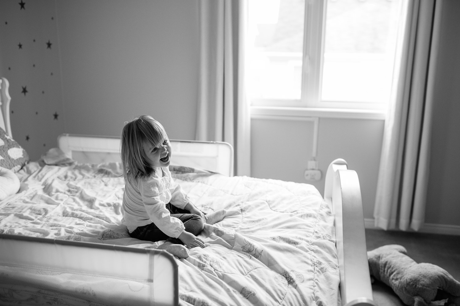 Markham In-Home Photography -little girl playing on her bed, classic black and white toddler image