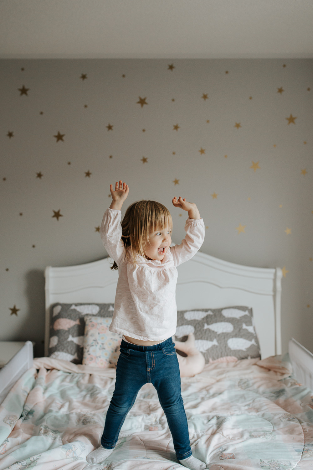 Blonde 2 year old toddler girl standing on bed with hands in the air, big smile on her face -GTA In-Home Photography