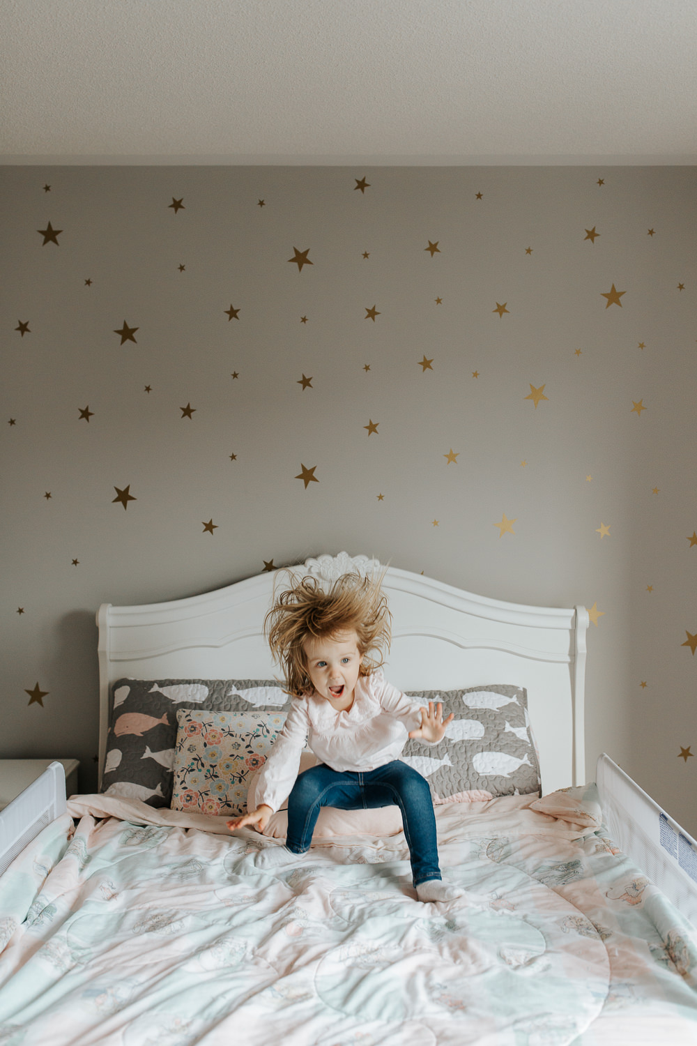Blonde 2 year old toddler girl jumping on bed, hair flying in the air, big smile on face -York Region In-Home Photography