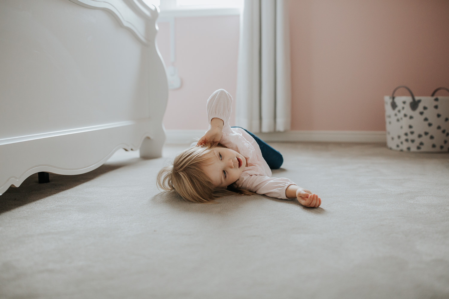 2 year old toddler girl lying on the floor of her pink coloured bedroom - Markham In-Home Photos