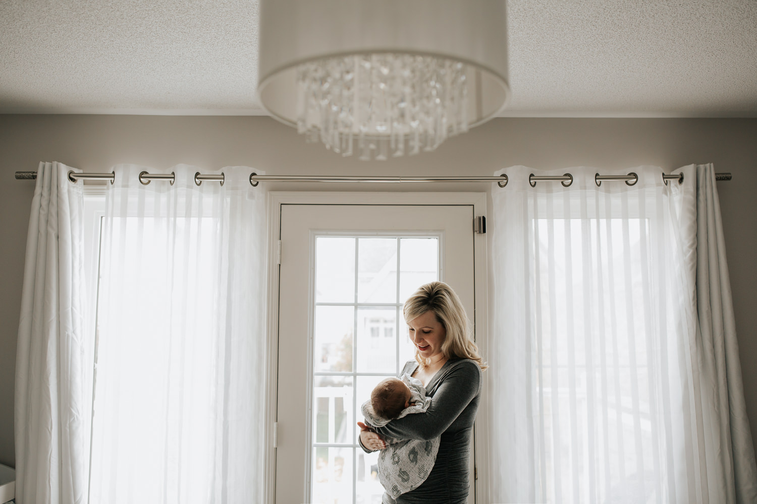 GTA In-Home Photos  - blonde mom adoring her new 2 week old baby boy standing by the door with a crystal chandelier up above