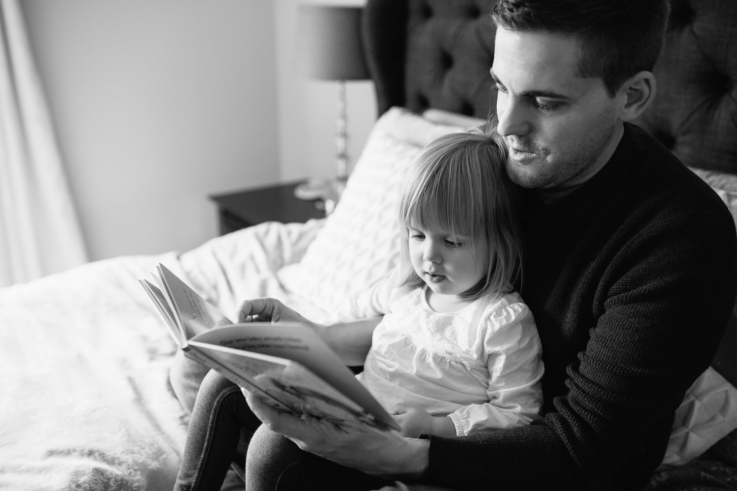 2 year old toddler girl sitting in father's lap on master bed reading a story book - York Region In-Home Photos