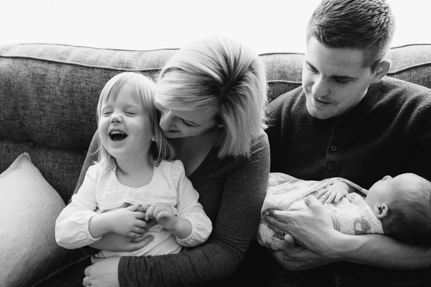 - family of four smiling together on a living room couch, 2 week old baby boy in dad's arms, toddler girl in mom's lap, daughter laughing as mother hugs her - Newmarket Lifestyle Photography