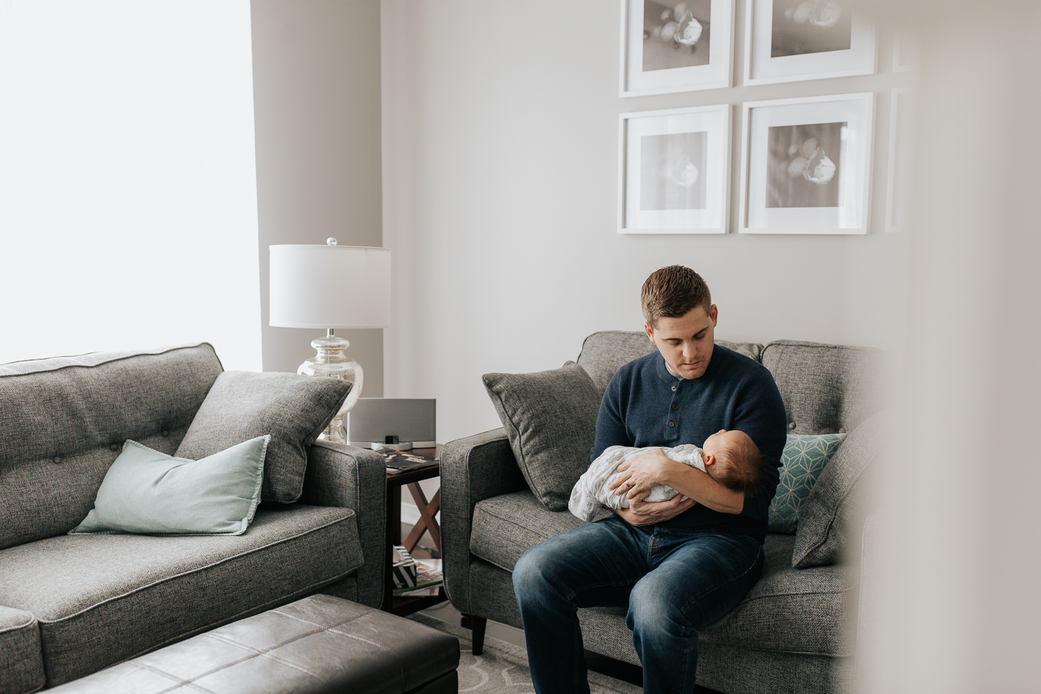 father sitting on couch holding sleeping 2 week old baby boy in his arms, looking at son -  Stouffville Lifestyle Photography