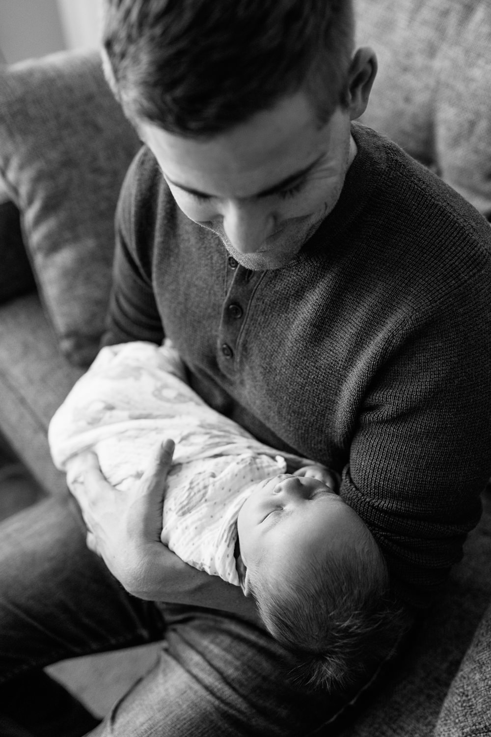father sitting on couch holding sleeping 2 week old baby boy in his arms, looking at son - Barrie Lifestyle Photography