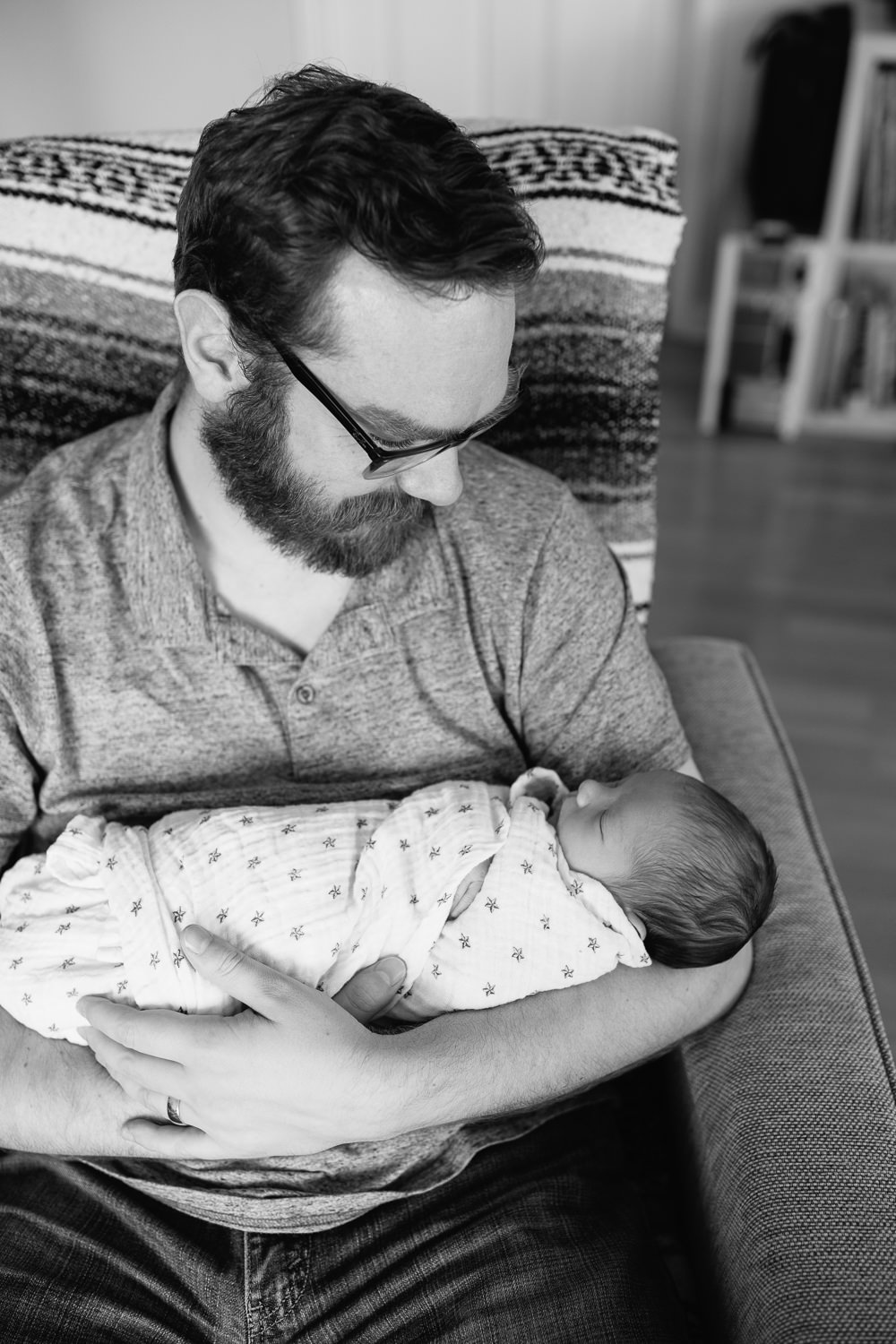 new father sitting in chair holding sleeping 2 week old baby boy in swaddle with dark hair -Newmarket In-Home Photos